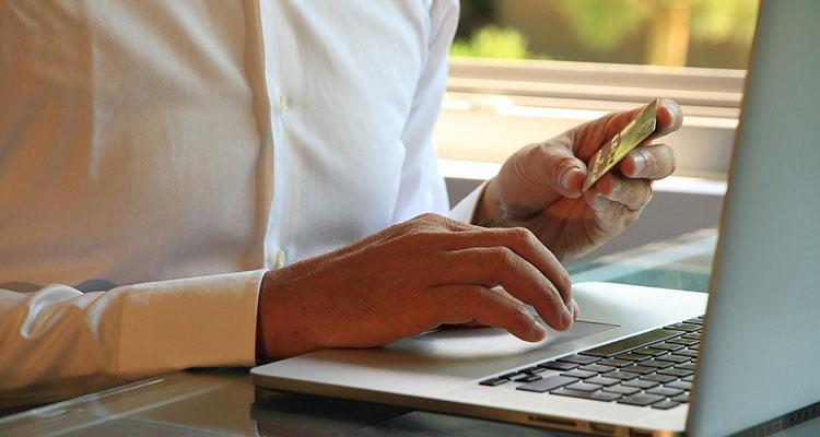 Persona pagando online con una tarjeta de crédito
